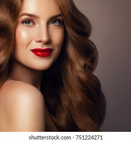 Perfect Redhead Woman with Beautiful Curly Hairstyle and Makeup. Elegant Model with Long Healthy Hair Smiling