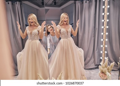 It is perfect.  Reflection of attractive young woman adjusting a wedding dress on a bride while standing in the fitting room