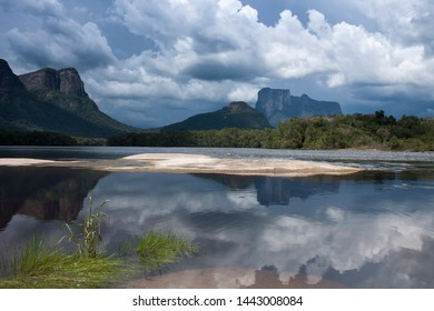 Perfect reflection of Cerro Autana with dramatic cloud in the back, in calm river in the jungle of amazonia