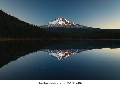 A perfect reflection of Mt. Hood in the early morning sunrise as ripples go in the foreground.