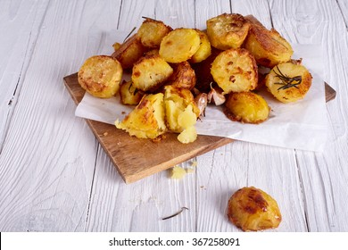 Perfect roasted potatoes with spices and herbs on wood board