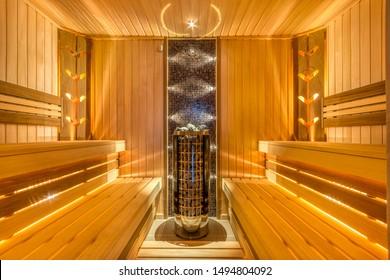 sauna perfecta con calentador eléctrico, paredes de paneles de madera y bonita iluminación
