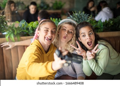 The perfect scenery. Three girls in cafe using camera. Focus is on background.