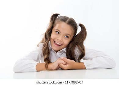 Perfect schoolgirl with tidy fancy hair. School hairstyle ultimate top list. Prepare kid first school day. Schoolgirl happy carefree face cute ponytail. Excellent pupil lean on desk isolated white.