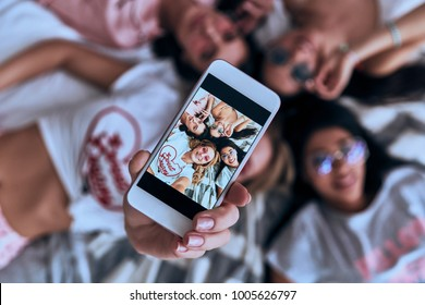 Perfect selfie. Top view of four playful young smiling women in eyewear taking selfie with smart phone while lying on the bed at home