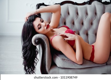 Perfect, sexy body, legs and ass of young woman wearing seductive red lingerie. Beautiful hot female in underware posing on luxury vintage sofa