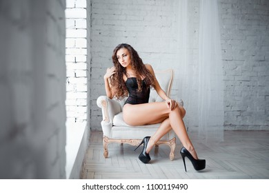 Perfect, sexy body, legs and ass of young woman wearing seductive lacy black lingerie. Beautiful hot female in bodysuit posing on luxury vintage chair