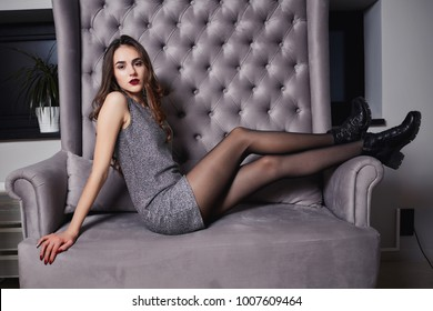 Perfect, sexy body, legs of young woman wearing gray dress. Sensual girl posing on sofa in erotical way. Attractive pretty young woman sitting on sofa couch. Elegant fashionable gorgeous girl. Fashion