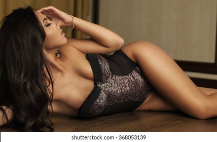 Perfect sexy tan woman with perfect skin , big full lips posing at bedroom, wearing sexy luxury stylish black dress.