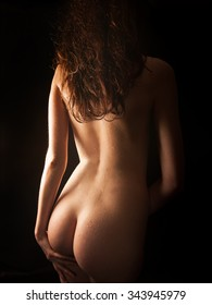 Perfect shape of an attractive nude woman in front of black studio background