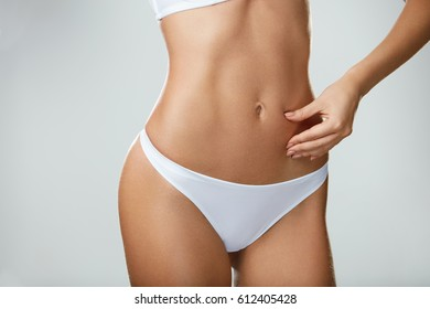 Perfect Shape. Hot Slim Young Woman Body In White Panties Posing On Grey Background. Closeup Of Female Hand Pinching Fit Pumped Belly, Abdomen. Fitness Concept. High Resolution