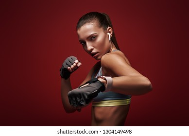Perfect shape. Young sportswoman standing over red background is ready to exercise