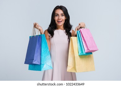 Perfect shopping. Beautiful young woman holding shopping bags and looking at camera with smile while standing against white background