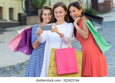 Perfect shopping with a smile. Three young and pretty girls are holding the shopping bags and making selfie on a sell phone. Happy shopping with smiles. Mall and sales