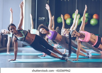 Perfect side plank. Full length of young beautiful women with perfect bodies in sportswear doing side plank and looking at camera with smile at gym