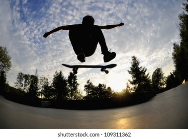 perfect silhouette of a skateboarder doing a flip trick at the skate park.