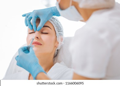 Perfect skin. Skilled experienced beautician looking at her clients face while doing an injection in the nose