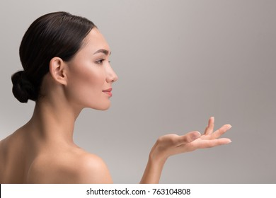 Perfect skincare and beauty concept. Side view profile of positive attractive young asian woman is holding palm up and looking ahead with slight smile. Isolated with copy space in the right side
