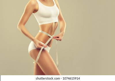 Perfect slim toned young body of the girl . An example of sports , fitness or plastic surgery and aesthetic cosmetology.Woman measuring her waist over white background