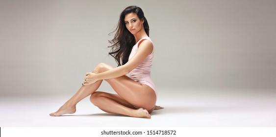 Perfect slim toned young body of brunette sensual girl, fit woman at studio. The fitness, diet, sports, plastic surgery and aesthetic cosmetology concept. Long legs.