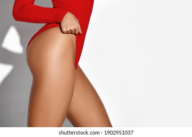 Perfect slim toned young body of the girl legs and hip wear red body swimsuit . An example of sports , fitness or plastic surgery and aesthetic cosmetology on a white background