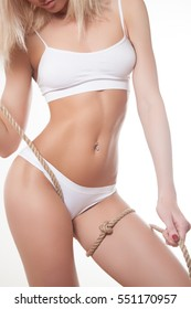 Perfect slim toned young body of the girl . Athletic body. Plastic surgery . The perfect body and skin. Girl with rope. Sexy girl.