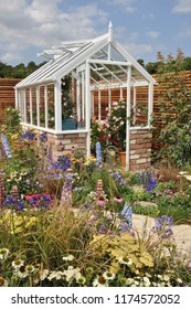 Perfect small wooden greenhouse in colorful English cottage flower garden.