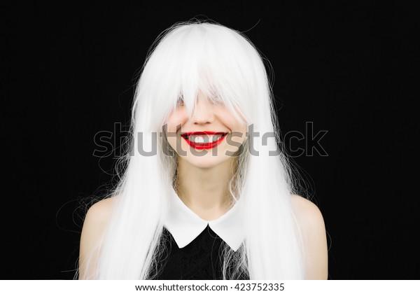 Femme folle de sourire parfaite, perruque blanche aux lèvres rouges. Fun girl avec de belles dents blanches, style enseignant. Jeune fille joyeuse s'amusant. Maquillage clair et coiffure sur fond noir isolé.