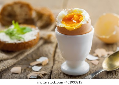 Perfect soft boiled egg and open bread sandwich with butter and dill on a table. Traditional food for healthy breakfast.
