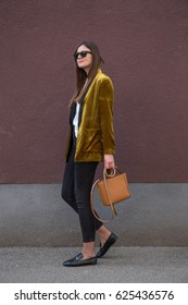 perfect spring fashion outfit. european fashion blogger wearing a trendy mustard velvet blazer, black jeans, fishnet stockings and black loafers. holding a stylish handbag.