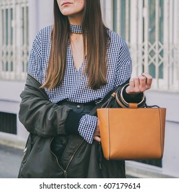 perfect spring fashion outfit. fashionable young woman wearing a gingham check top, black skirt,  bomber jacket and a brown handbag. fashion blogger posing on the street.
