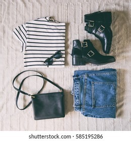 perfect spring outfit. flat lay of a trendy fashion outfit, sunglasses, denim jeans, striped shirt, black ankle boots and a small elegant black purse. top view.
