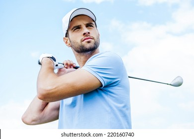 Perfect strike. Low angle view of young golfer swinging his driver and looking away with blue sky as background