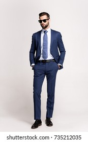 Perfect style. Full length of handsome young man in suit and glasses looking away while standing against white background.