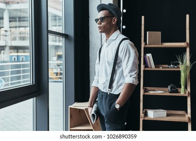 Perfect style. Handsome young man looking away and keeping hand in pocket while standing near the window