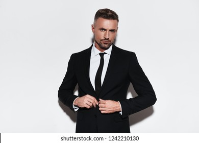 Perfect style. Handsome young man in full suit buttoning his jacket and looking at camera while standing against white background