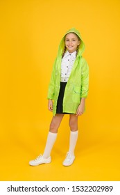 Its the perfect style for your little schoolgirl. Happy schoolgirl on yellow background. Small schoolgirl wear raincoat and hood for rainy day. Cute schoolgirl feel protected for autumn weather.