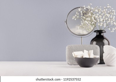 Perfect stylish decoration for home in grey colors - black glass vase with small fluffy flowers, mirror, female silver cosmetic bag, bowl sponges on soft ligth white wood table.