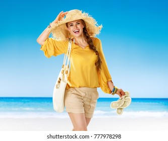 Perfect summer. Portrait of smiling young woman in shorts and yellow blouse with white beach bag on the seashore holding summer slippers