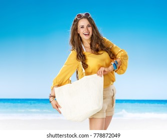 Perfect summer. smiling active woman in shorts and yellow blouse with white beach bag on the beach showing white beach bag as copy space