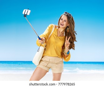 Perfect summer. smiling young woman in shorts and yellow blouse with white beach bag on the seashore taking selfie using selfie stick and showing victory