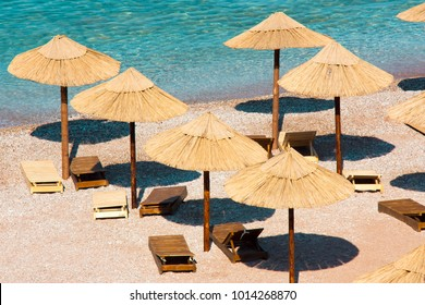 Perfect summer vacation destination : Straw sunshades and sunbeds on the empty pebble beach  with sea  in the background , high angle view