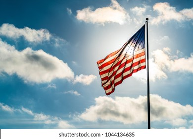 Perfect sunny day with puffy white clouds and direct sunshine into the perfect American flag illuminated back lit by sun. United States flag waving in the wind on a dramatic sky day direct sunshine