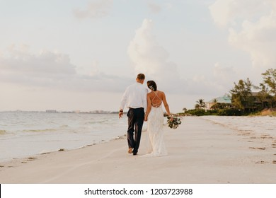 Perfect Sunset Destination Beach Wedding with Beautiful Bride and Groom Walking Down the Coastline
