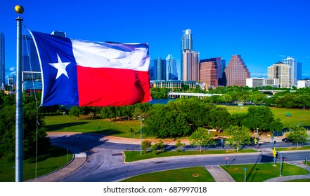Perfect Texas Flag Flying over Lone Star State Capital City with a Colorful Austin Texas Skyline Cityscape Background on a Nice Sunny Summer Blue Sky Day Aerial Drone View