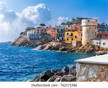 "The perfect tiny seaside village of ""Giglio Porto"", with multi colored houses, an ancient defensive tower  and a rocky coastline against a deep blue Mediterranean sea. - Giglio Island, Tuscany, Italy"