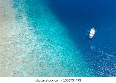 Perfect tropical island paradise beach Maldives. Amazing coral reef and beautiful aerial view of blue sea and shallow water with a traditional boat Dhoni. Luxury Maldives vacation concept