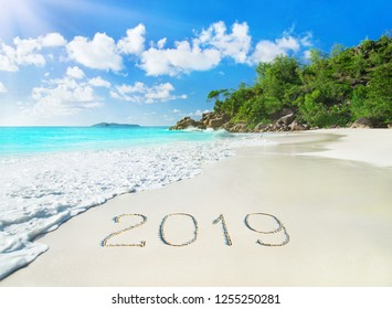 Perfect tropical palm sandy beach Anse Georgette at Praslin island, Seychelles - travel vacation season new year 2019 background, caption handwritten on sand, against waves, blue sky and forest