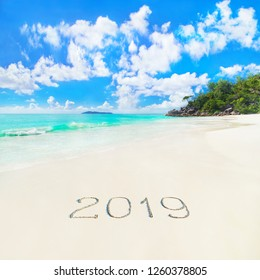 Perfect tropical palm sandy beach Anse Georgette at Praslin island, Seychelles, caption 2019 year handwritten on sand against waves, blue sky and forest. New tourist season background