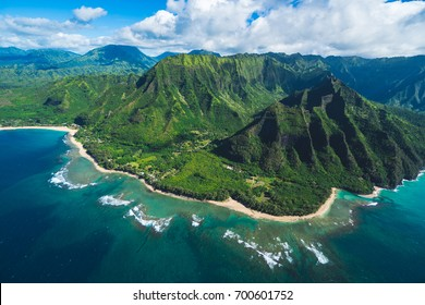 Perfect view of the east side of Kauai, Princeville area from a helicopter with lush green mountain and garden in the background, ocean in the foreground